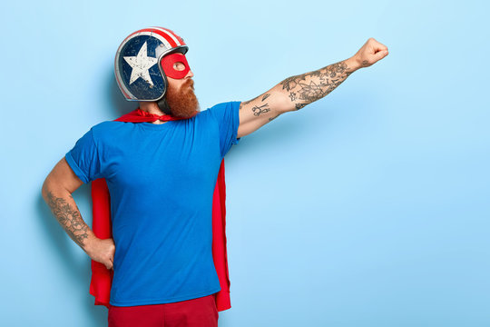 Profile shot of serious bearded man makes flying gesture, looks into distance, wears protective helmet and red cape, poses against blue background with empty space for your promotional content