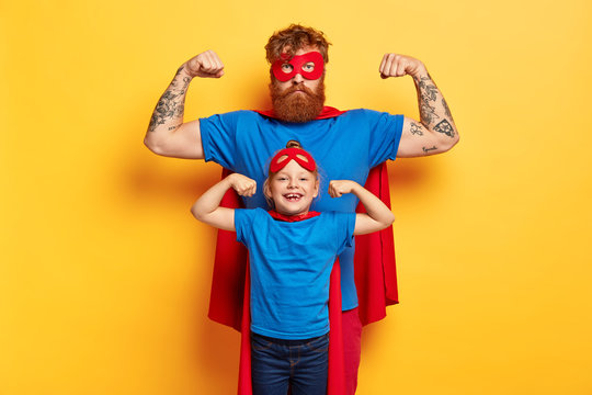 Superhero family. Strong father and small child show biceps, pretend being superman, wear red masks, blue t shirts and cloaks, motivated for successful future, stand agaisnt yellow studio wall