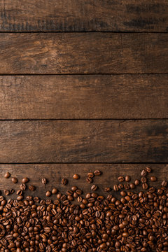 Coffee beans on wooden background with copyspace.