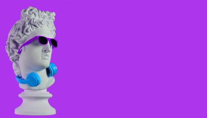 Statue. Earphone on a purple background. Gypsum statue of David's head. Creative. Plaster statue of...