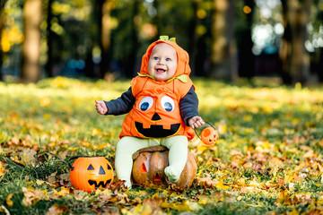 Cheerful little baby boy in halloween costume sitting on pumpkin, celebration Wall mural
