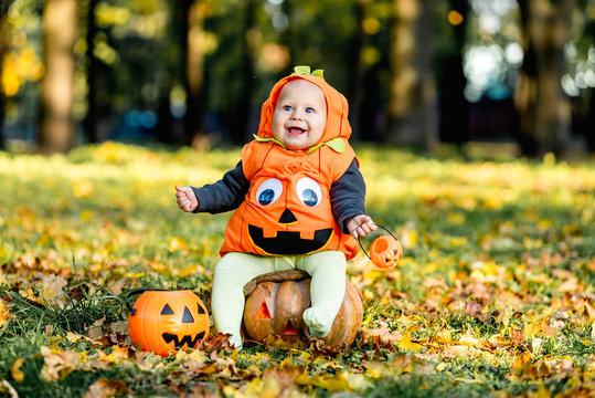 Cheerful little baby boy in halloween costume sitting on pumpkin, celebration