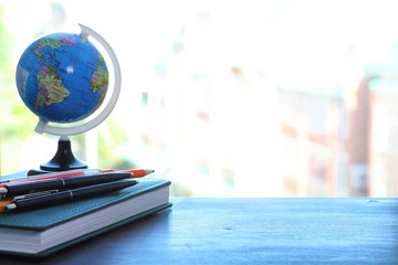 A pen on the desk and a small globe