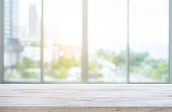 Wood table top on blur window glass,wall background with city view