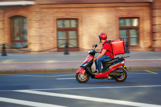 Delivery boy of takeaway on scooter with isothermal food case box driving fast. Express food delivery service from cafes and restaurants. Courier on the moto scooter delivering food.