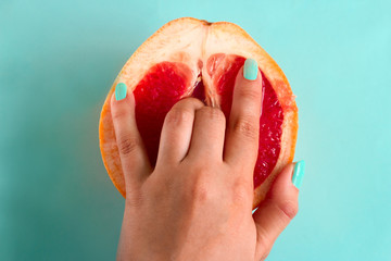 two fingers in a grapefruit isolated on a blue background top view sex concept Wall mural