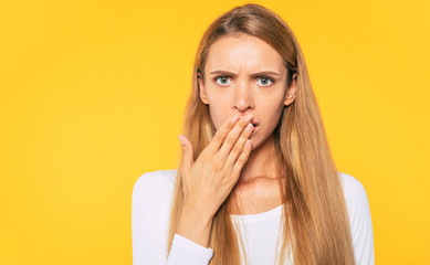Shocked face of beautiful blonde woman with closed mouth with help of her hands isolated on yellow