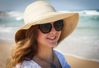 Happy beautiful young Caucasian Russian woman in her late 20s in a straw hat with sunglasses on a hot summer day at the seaside with sea waves on her background. Summer vacation at the sea concept