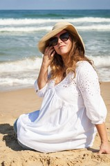 Happy young pregnant Caucasian woman at the seaside enjoying life. Pregnancy not a burden concept. Beautiful pregnant lady in a white dress and straw hat by the sea. Lifestyle concept image.