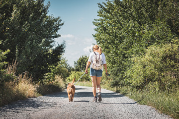 Obraz Woman and dog walking on road. Tourist with backpack enjoying walk with her animal best friend - fototapety do salonu