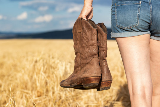 Woman holding cowboy boots in field