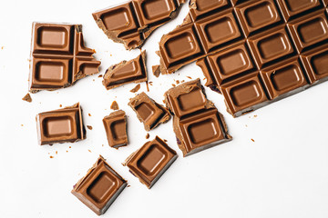 Broken chocolate bar on white background, top view