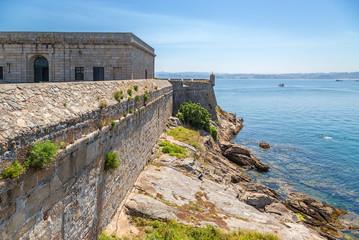 La Coruna, Spain. The fortress wall of the castle of San Anton on the rocky shore