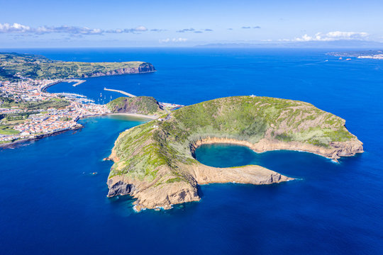 Nature Park of destructed extinct volcano craters of Caldeirinhas, mountain Guia, bay Baia do Porto Pim and port, beaches, marinas, red roofs of historical Horta city, Faial island, Portugal
