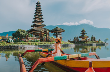 Tuinposter Bali Beautiful girl kayaking on the catamaran at the ulun datu pura bratan temple, in Bali
