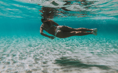 Woman swimming underwater. Concept about vacations and nature. Shot taken with under water action camera
