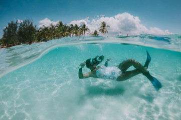 Beautiful woman swimming underwater in a tropical sea full of corals. under water shot with action camera. concept about wanderlust travels Fototapete