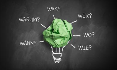 """Papierkugel als Glühlampe und Fragewörter """"wer, wie, wo, was, warum, wann"""" auf Kreidetafel"""
