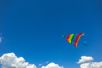 Colourful small kite flying in bluy sunny bright sky. Horizontal color photography.