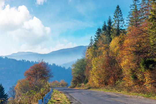 old cracked asphalt road in mountains. straight path along the forest on hill. trees in fall colors. distant ridge in haze. sunny autumn weather with fluffy clouds on the bright blue sky