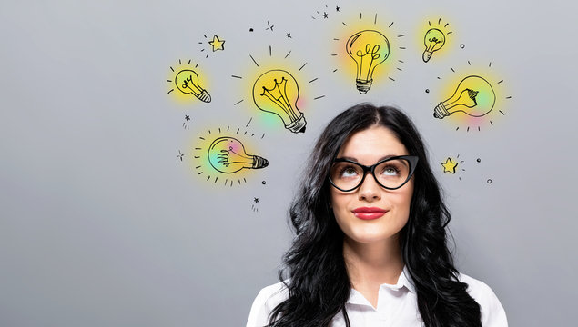 Idea light bulbs with young businesswoman in a thoughtful face
