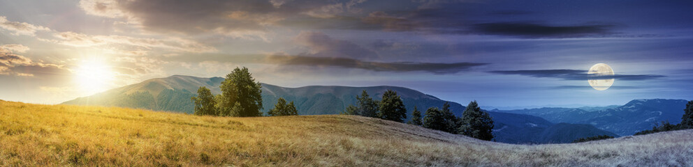 beautiful panoramic landscape in august. row of beech trees on the meadow in weathered grass. mountain range in the distance with sun and moon on the sky. day and night time change concept