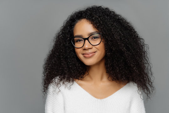 Close up portrait of delighted beautiful Afro woman with bushy curly hair, looks through transparent glasses, wears white sweater, poses against grey studio wall. Ethnicity, beauty, facial expressions
