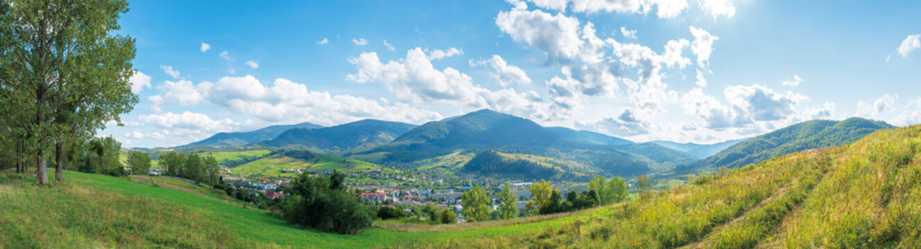 beautiful rural area of carpathian mountains. trees and agricultural fields on hills. panoramic landscape in dappled light. forest on the distant ridge. sunny weather with clouds on the afternoon sky
