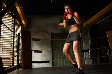 Dramatic full length portrait of tough female boxer practicing in boxing ring, copy space
