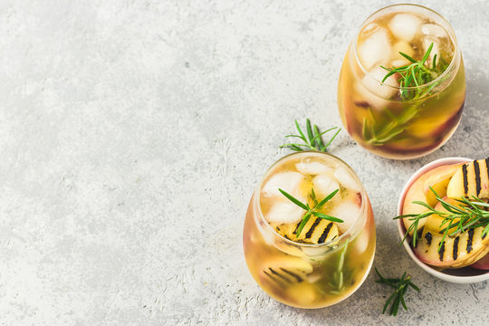 Cold brew grilled nectarines rosemary iced tea. Top view, space for text.
