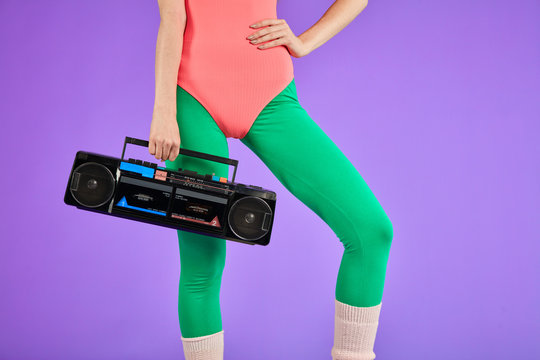 fitness girl stands in comfortable pink bodysuit and green leggins with one hand holding portable retro audio player and other is on her waist, has nice body curves and well-shaped