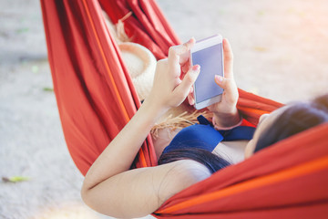 Crop image of woman in bikini using mobile phone in red hammock on tropical beach. Summer and vacation concept