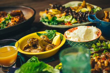 Feast of chicken dishes, salad and pap on a wooden deck
