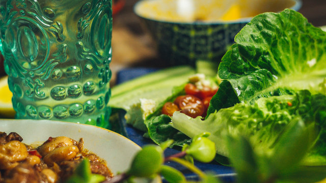 Salad Lettuce Leaves with a Chicken Dish and a Glass of Water