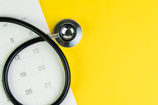 Medical and health care calendar, reminder, schedule or appointment concept, doctor's stethoscope on white clean calendar with date on solid yellow background with copy space