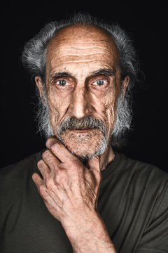 thin mad skinny old man in green T-shirt with a palm on the chin looking at the camera with scared expression. close up portrait. isolated black background, studio shot, fear, fobia.