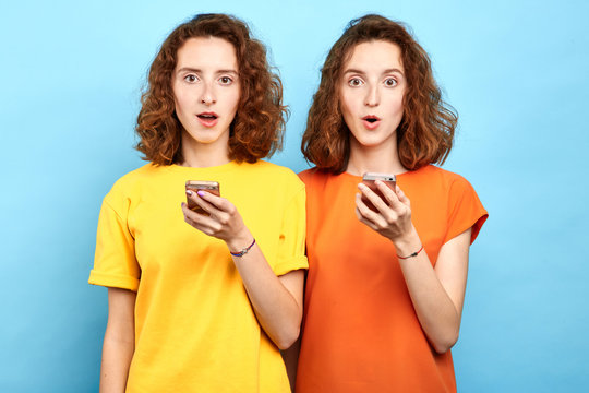 surprised emotional twins with wide open mouth and bugged eyes holding smart phones and looking at the camera. sale, business, free message, double discounts