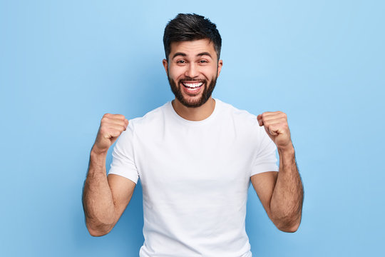 excited Arab man celebrating success with two fists in air isolated on the blue background. close up portrait, studio shot , happiness, positive emotion and feeling. I've done it. facial expression