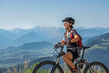 nice, active senior woman underway with her electric mountain bike in the Allgaeu Alps near Oberstdorf, Bavarian Alps, Germany Wall mural