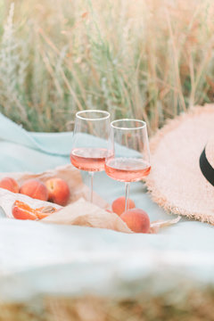 Two glasses of red wine, apricots and peaches on the sunset picnic.