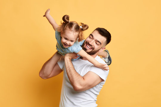 cheerful happy man teaching sweet lovely daughter to fly like a plane. close up photo. isolated yellow background. studio shot, happy moments with best father