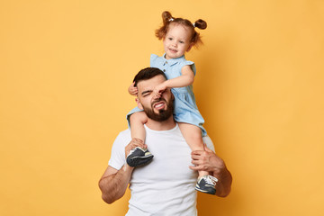 Fototapeta naughty girl holding her daddy's nose, display negative, angry behaviour. close up photo. isolated yellow background.father cannot manage with naughty behaviour obraz