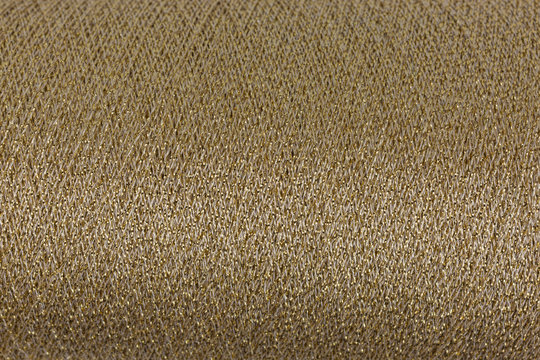 background of golden and white lurex wool on a cone