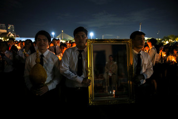 Well-wishers hold a picture of Thai King Maha Vajiralongkorn to celebrate the king's 67th birthday outside the Grand Palace in Bangkok
