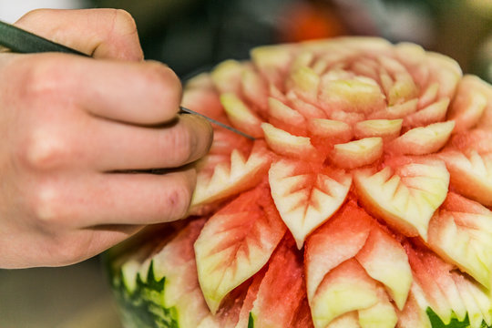 Close up crafts carved watermelon with the hand and carving knife