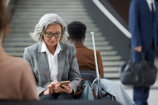 Content elderly Asian woman with gray hair wearing eyeglasses sitting in waiting area of airport and using mobile app on gadget