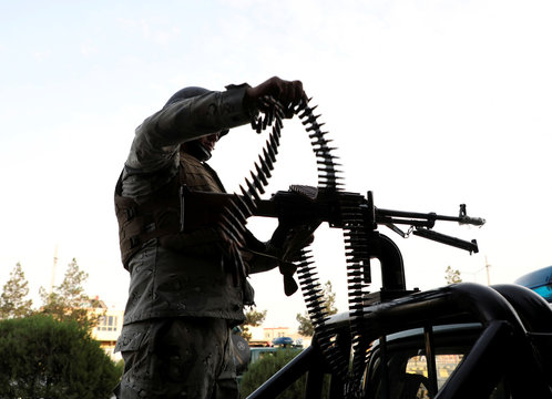 A member of Afghan security forces loads a machine gun near the site of a powerful blast in Kabul
