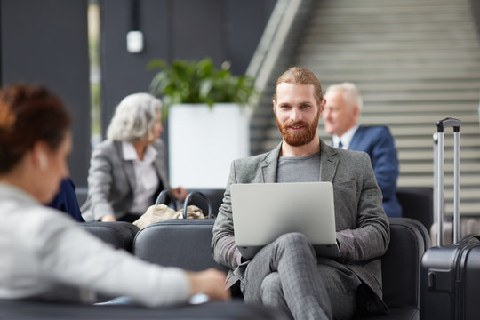 Portrait of smiling red-bearded entrepreneur in gray jacket sitting on sofa and using laptop in airport