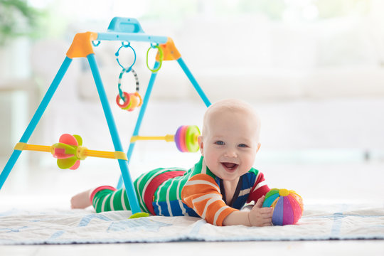Baby boy with toys and ball