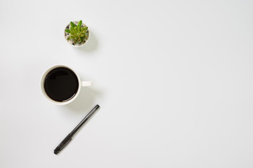 Wall Mural - Flat lay, top view office table white desk. Workspace with notepad, pen, green leaf, and coffee cup on white background.